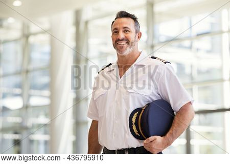 Smiling pilot in uniform standing at airport. Mature man wearing airplane uniform ready to fly at gate. Experienced commercial airplane pilot in uniform at modern airport smiling with copy space.