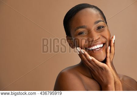 Beautiful face of mature smiling woman with clean fresh skin isolated against brown background. African middle aged woman touching cheeks and looking at camera. Mid adult black lady holding her cheeks