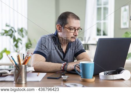 Young Freelance Man Working On Laptop Computer From Home