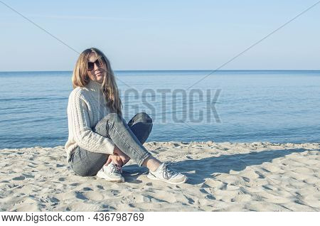 White Caucasian Woman In Sweater And Sunglasses Sitting On A Sand Shore Near The Baltic Sea In Grey