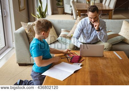 Caucasian father using laptop while son doing his homework at home. home schooling and working from home during coronavirus covid-19 pandemic concept