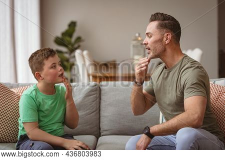 Caucasian father and son communicating using sign language while sitting on the couch at home. sign language learning concept