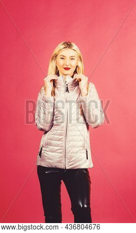 Studio Shot Of Pretty Carefree Woman Holds Hands On The Collar, Wears Jacket.