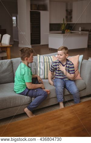 Two caucasian boys communicating using sign language while sitting on the couch at home. sign language learning concept