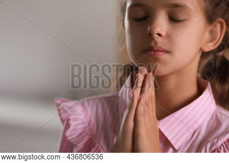 Cute Little Girl With Hands Clasped Together Praying On Blurred Background, Closeup