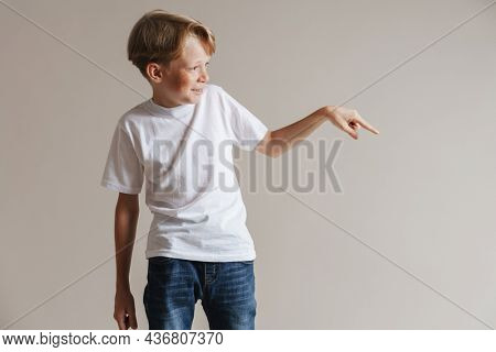 Portrait of a happy smiling casual preteen boy in t-shirt standing over isolated gray wall background presenting copy space
