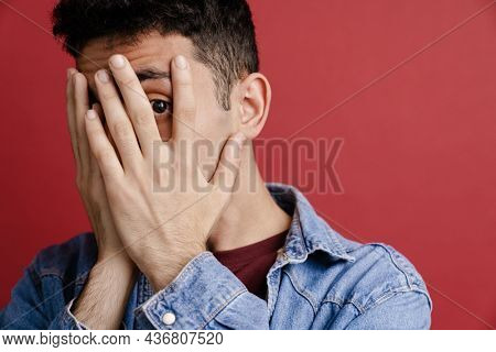 Young middle eastern man covering his face while looking at camera isolated over red background