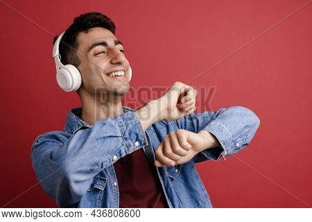 Young middle eastern man dancing while listening music with headphones isolated over red background