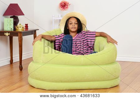 black child relaxing in green chair