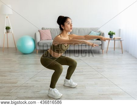 Full Length Of Sporty Young Indian Woman Doing Squats At Home