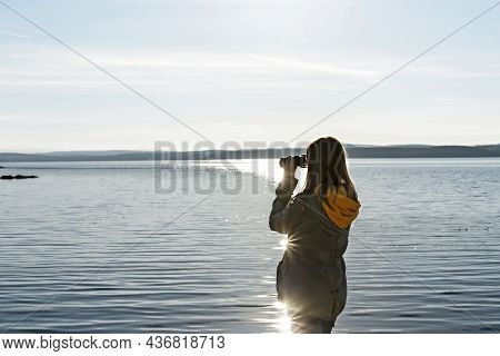 Young Woman Looking Through Binoculars At Birds On The Lake. Birdwatching, Zoology, Ecology. Researc