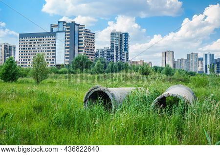 Remains Of Construction Pipes On A Green Meadow. Modern New Buildings In The Background