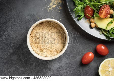 Gluten Free Nutritional Yeast Flakes In Ceramic Bowl. Ingredient For Vegan Food. Closeup, Copy Space