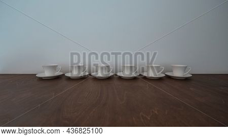 Six Little White Porcelain Cups for Tea isolated on the Kitchen Table. Time for Drinking Tea. Traditional Tea Party Utensil.