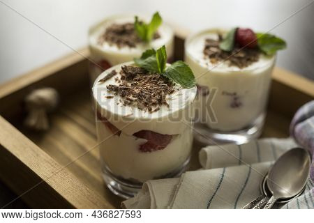 White Dessert With A Layer Of Strawberries In A Transparent Glass With Sprinkled, With Grated Chocol