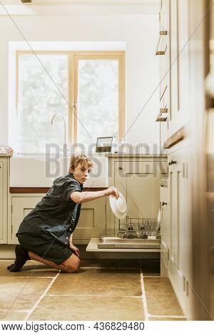 Boy loading dishwasher, basic house chores