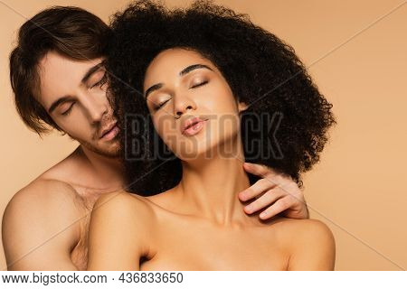 Young Man With Closed Eyes Hugging Passionate And Topless Latin Woman Isolated On Beige