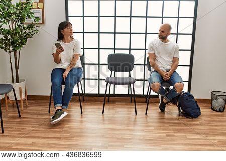 Two hispanic person boring using smartphone at waiting room.