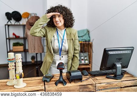Young middle eastern woman working as manager at retail boutique very happy and smiling looking far away with hand over head. searching concept.
