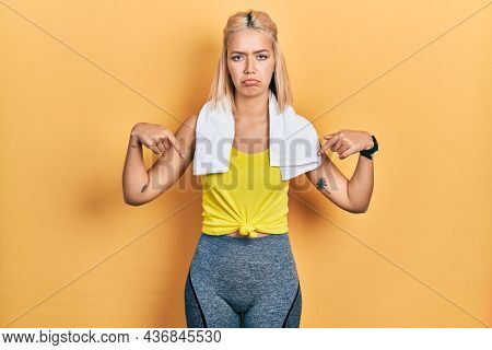 Beautiful blonde sports woman wearing workout outfit pointing down looking sad and upset, indicating direction with fingers, unhappy and depressed.