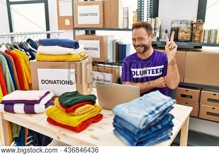 Middle age man wearing volunteer t shirt working with laptop smiling with happy face winking at the camera doing victory sign. number two.
