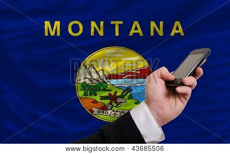 man holding cell phone in front flag of us state of montana symbolizing mobile communication and telecommunication poster