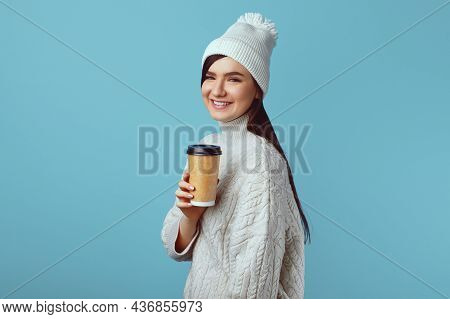 Winter Or Autumn Warming Up. Happy Caucasian Girl In White Hat And White Warm Sweater, Holds Takeawa