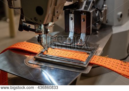 Powerful Sewing Machine Tool Operates With Bright Orange Car Towing Strap On Metal Workbench In Plan