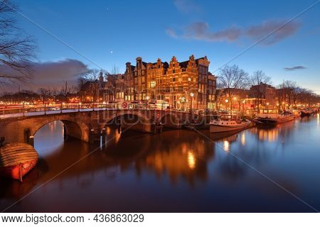 Amsterdam, Netherlands bridges and canals at twilight.