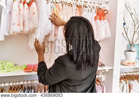 Hispanic woman working as shop assistant at children clothes small retail trade. Sales assistant smiling happy while holding shirt