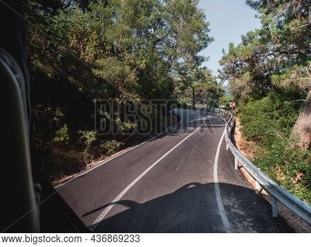 Travel Along The Mountain Roads Of Turkey By Bus. The Road Meanders Between Woodlands On A Sunny Day