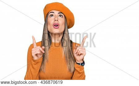 Young hispanic woman wearing french look with beret amazed and surprised looking up and pointing with fingers and raised arms.