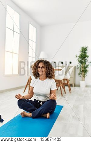Middle age hispanic woman smiling confident training yoga at home