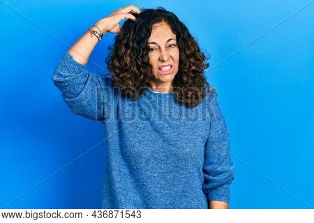 Middle age hispanic woman wearing casual clothes confuse and wonder about question. uncertain with doubt, thinking with hand on head. pensive concept.