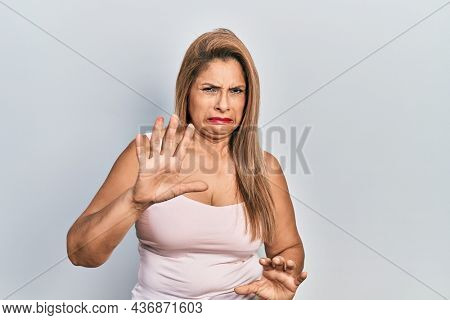 Middle age hispanic woman wearing casual style with sleeveless shirt disgusted expression, displeased and fearful doing disgust face because aversion reaction. with hands raised