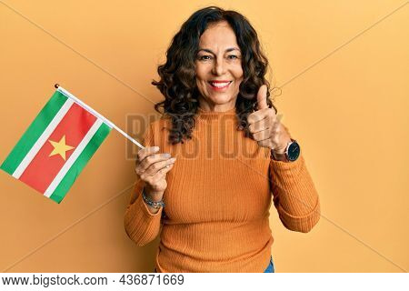 Middle age hispanic woman holding suriname flag smiling happy and positive, thumb up doing excellent and approval sign