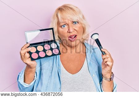 Middle age blonde woman holding makeup brush and blush in shock face, looking skeptical and sarcastic, surprised with open mouth