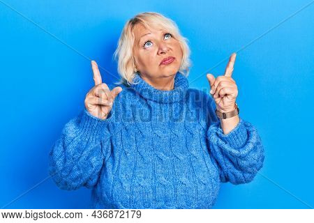 Middle age blonde woman wearing casual clothes pointing up looking sad and upset, indicating direction with fingers, unhappy and depressed.