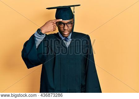 Young african american man wearing graduation cap and ceremony robe pointing unhappy to pimple on forehead, ugly infection of blackhead. acne and skin problem