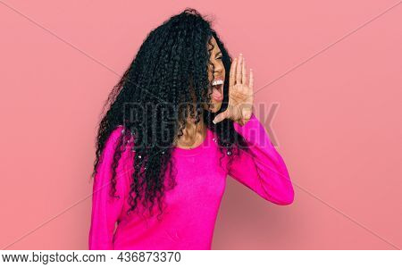 Middle age african american woman wearing casual clothes shouting and screaming loud to side with hand on mouth. communication concept.