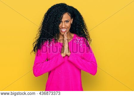 Middle age african american woman wearing casual clothes praying with hands together asking for forgiveness smiling confident.