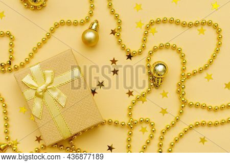 Christmas Composition Is Made Of Gift With Yellow Ribbon, Stars And Gold Beads And Christmas Balls O