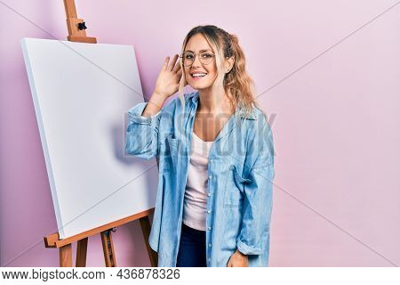 Beautiful young blonde woman standing by white painter easel stand smiling with hand over ear listening and hearing to rumor or gossip. deafness concept.