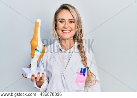 Beautiful young blonde doctor woman holding anatomical model of knee joint looking positive and happy standing and smiling with a confident smile showing teeth