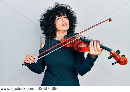 Young middle east woman playing violin in shock face, looking skeptical and sarcastic, surprised with open mouth