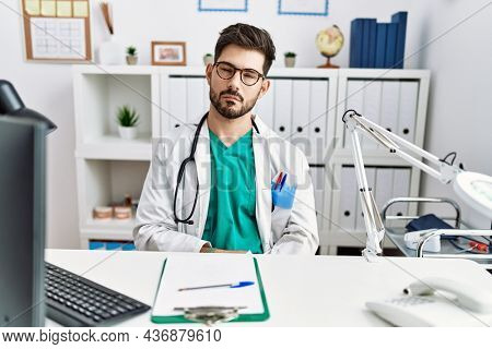 Young man with beard wearing doctor uniform and stethoscope at the clinic looking sleepy and tired, exhausted for fatigue and hangover, lazy eyes in the morning.