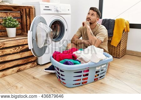 Young handsome man putting dirty laundry into washing machine with hand on chin thinking about question, pensive expression. smiling with thoughtful face. doubt concept.