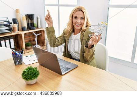 Beautiful blonde woman doing online shopping holding supermarket cart at the office smiling happy pointing with hand and finger to the side
