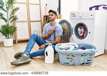 Young hispanic man putting dirty laundry into washing machine pointing aside worried and nervous with forefinger, concerned and surprised expression
