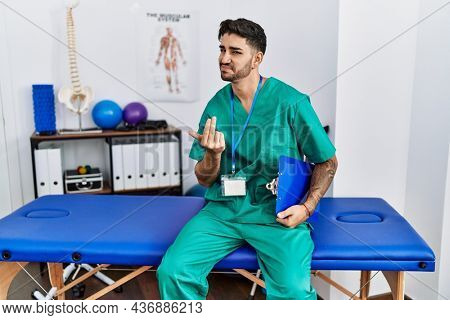 Young physiotherapist man working at pain recovery clinic beckoning come here gesture with hand inviting welcoming happy and smiling